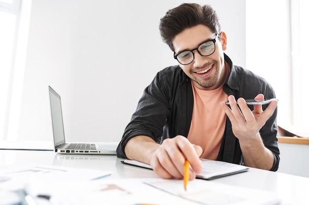 Un bell'uomo gioioso con gli occhiali che parla tramite smartphone e lavora con i documenti mentre è seduto al tavolo in ufficio