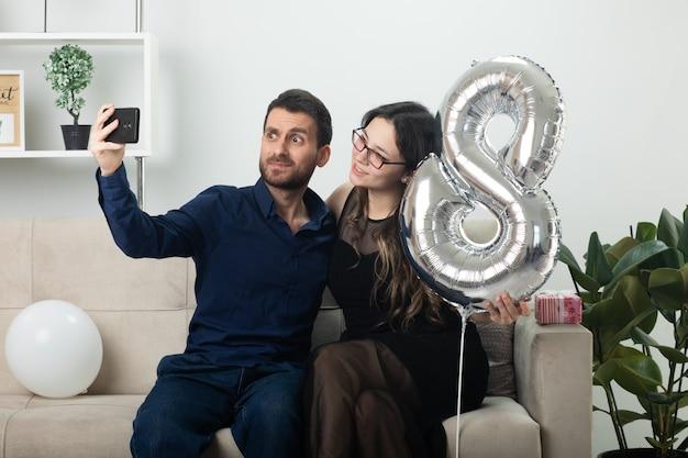 Gioioso bell'uomo che prende selfie al telefono con una bella giovane donna in occhiali ottici che tiene in mano un palloncino a forma di otto e seduto sul divano in salotto a marzo giornata internazionale della donna