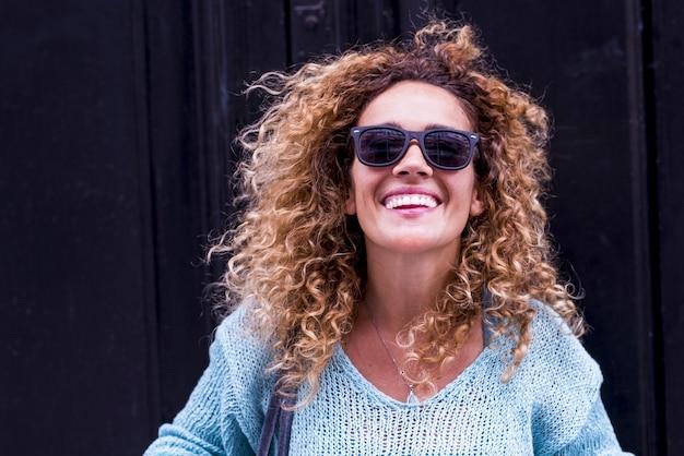 Gioioso e il concetto di felicità con allegra bella donna caucasica adulta sorridere e ridere davanti alla telecamera e muro nero in superficie