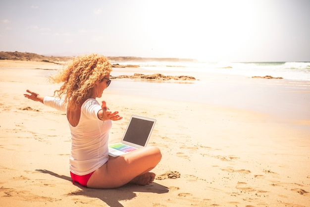 Lavoro gioioso e felice relativo ai giovani moderni che lavorano fuori ufficio nel mondo - bella donna di successo con computer portatile collegato in spiaggia con vista mare