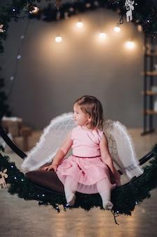 Bambino gioioso e felice che si siede e posa sulla corona di abete decorata con ghirlanda leggera