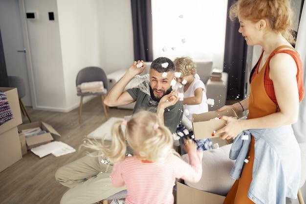 Gioiosa famiglia felice che gioca con la schiuma di plastica