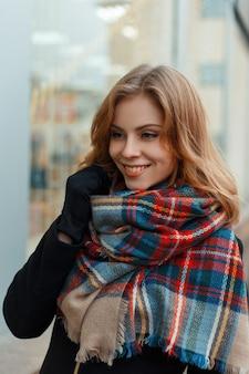 Gioiosa giovane donna felice in una sciarpa di lana calda alla moda in un elegante cappotto nero in guanti neri è in piedi e sorridente vicino alla finestra decorata con una ghirlanda. ragazza allegra.