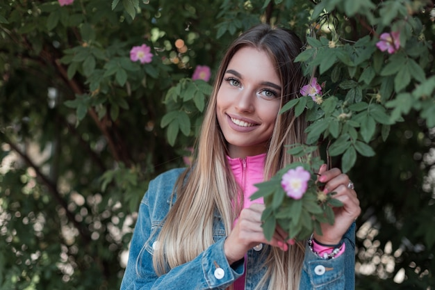 Gioiosa giovane donna felice con un bel sorriso con i capelli lunghi in una giacca di jeans blu alla moda si rilassa vicino a un cespuglio con fiori all'aperto in città. la ragazza attraente allegra gode del fine settimana estivo.