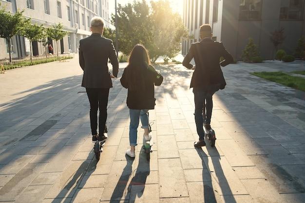 Gioiosi amici internazionali in possesso di scooter elettrici andando vicino a un edificio moderno