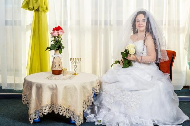 Una gioiosa sposa ebrea con il viso coperto da un velo con un mazzo di rose bianche siede in una sinagoga prima di eseguire la cerimonia huppa a un tavolo con fiori. foto orizzontale