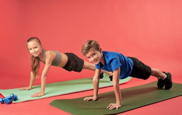 Bambini allegri che fanno esercizio di plancia su sfondo rosso