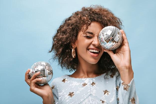Signora gioiosa con capelli ondulati bruna in abito blu elegante e orecchini d'oro che sorride e posa con palle da discoteca sul muro isolato