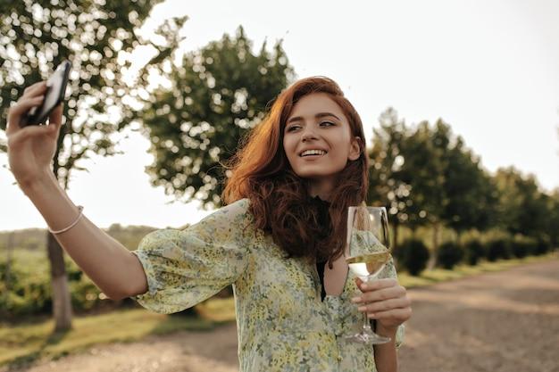 Signora gioiosa con acconciatura rossa e benda sul collo in abito stampato alla moda che fa selfie e tiene in mano un bicchiere con vino all'aperto