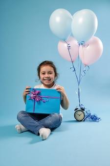 Bambina allegra carina sorridente nella parte anteriore seduto su una superficie blu accanto a una sveglia e palloncini e che tiene un regalo blu con un fiocco rosa