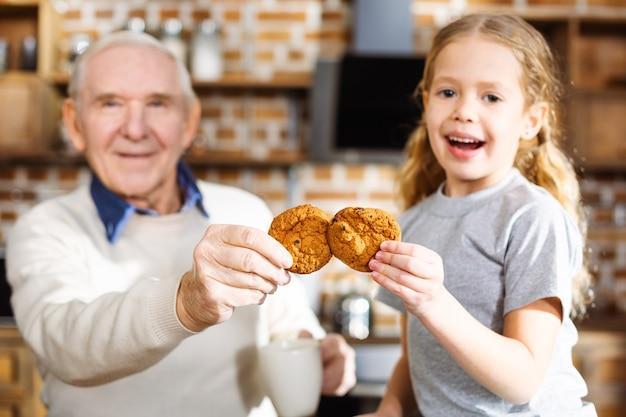 Bambina allegra che mangia i biscotti con suo nonno mentre riposa insieme a casa