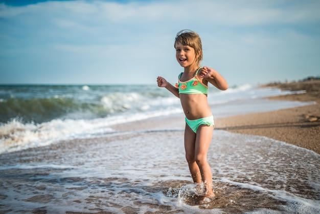 Bambina allegra gode di una giornata in spiaggia mentre ci si rilassa in mare in una soleggiata giornata estiva calda