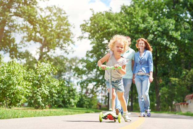 Gioiosa bambina sorridente in sella a uno scooter al parco con i suoi genitori che camminano sullo sfondo copyspace famiglia weekend vacanza attività genitorialità infanzia concetto.
