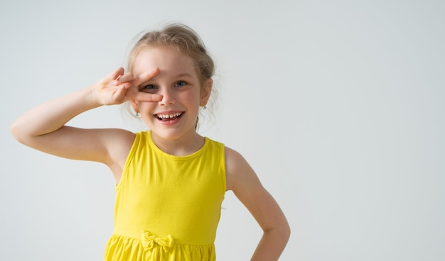 Bambina allegra con un sorriso adorabile lucido che guarda attraverso le sue due dita allargate che tengono la mano sull'anca.