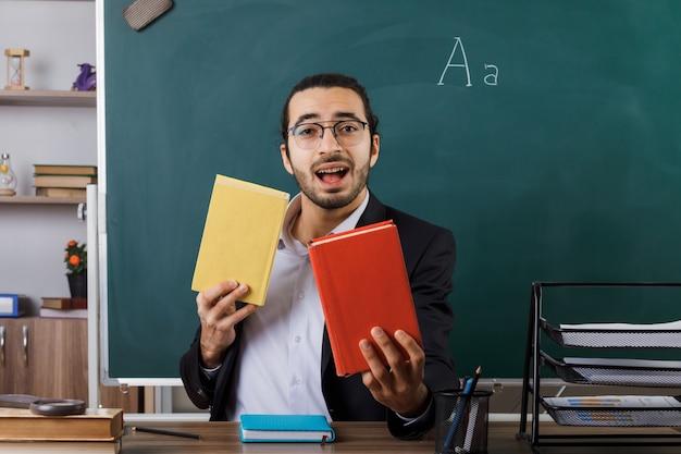 Insegnante maschio gioioso con gli occhiali che tiene fuori il libro seduto al tavolo con gli strumenti della scuola in classe