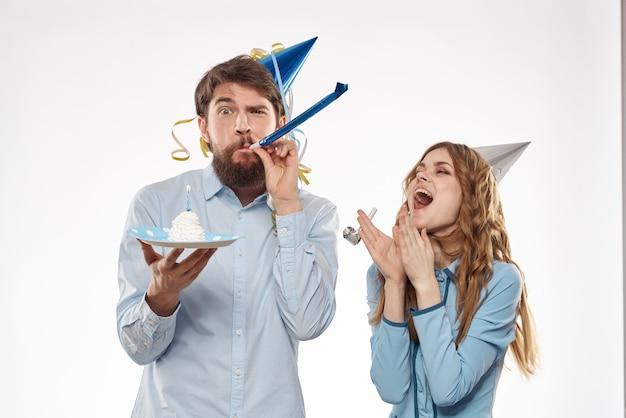 Gioioso uomo e donna allegra vacanza torta di compleanno cap festa festa aziendale giovani