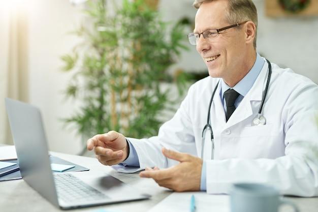 Medico gioioso seduto al tavolo con il computer portatile e sorridente mentre parla con il paziente online
