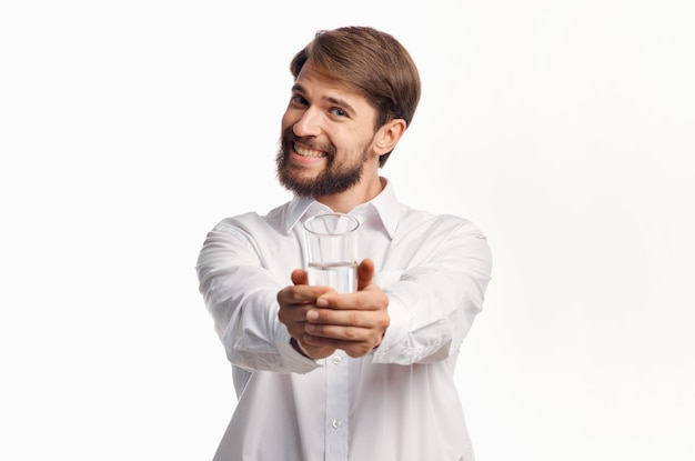 L'uomo allegro allunga la mano con un bicchiere d'acqua in avanti su uno sfondo chiaro