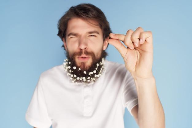 Uomo allegro in camicia bianca barba fiori decorazione stile di vita sfondo blu. foto di alta qualità