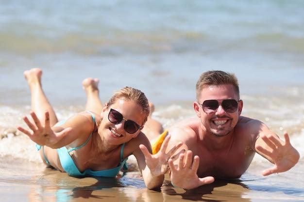 L'uomo e la donna allegri in occhiali da sole si trovano sulla sabbia bagnata vicino al mare