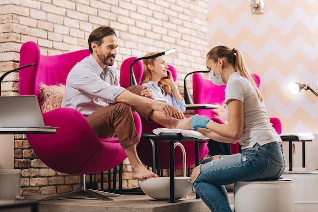 Uomo maturo allegro che ottiene le unghie dei piedi fatte e che si siede sulla sedia