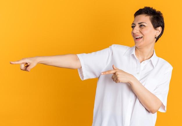 Gioiosa donna di mezza età che ti guarda di lato facendo un gesto di risata