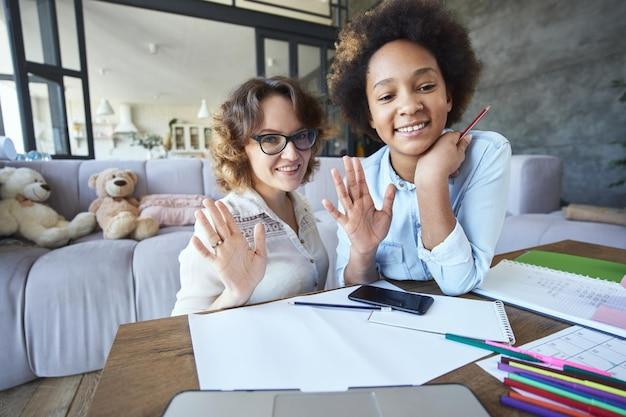 Gioiosa ragazza adolescente di razza mista e insegnante che salutano la telecamera mentre fanno i compiti insieme in