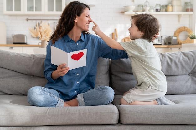 La mamma gioiosa che ride gioca con il figlio carino tiene una cartolina regalo per il compleanno o la festa della mamma seduta sul divano