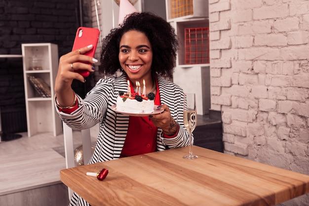 Momenti gioiosi. bella donna felice tenendo una torta mentre si scatta una foto con esso