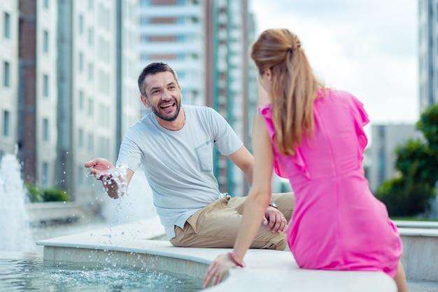 Stato d'animo gioioso. uomo felice felice che gioca con l'acqua mentre guarda la sua ragazza
