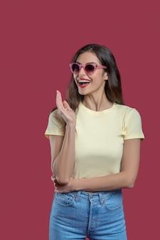 Stato d'animo gioioso. felice giovane donna sottile in occhiali da sole con la bocca aperta in jeans e maglietta in piedi su sfondo rosa