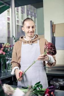 Stato d'animo gioioso. gentile giovane fioraio che esprime positività mentre prepara i fiori per il bouquet