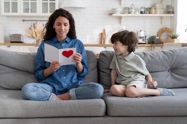 La mamma gioiosa legge gli auguri per il compleanno o la festa della mamma dal biglietto di auguri fatto a mano dal figlio piccolo