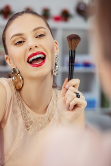 Gioiosa bella donna che sorride al suo riflesso mentre tiene in mano un pennello per il trucco