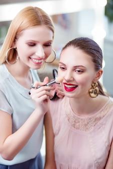 Gioiosa bella donna che sorride mentre tocca il naso dei suoi clienti con un pennello