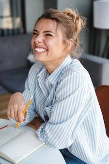 Gioiosa bella donna che scrive sul diario e ride mentre è seduta a tavola in soggiorno