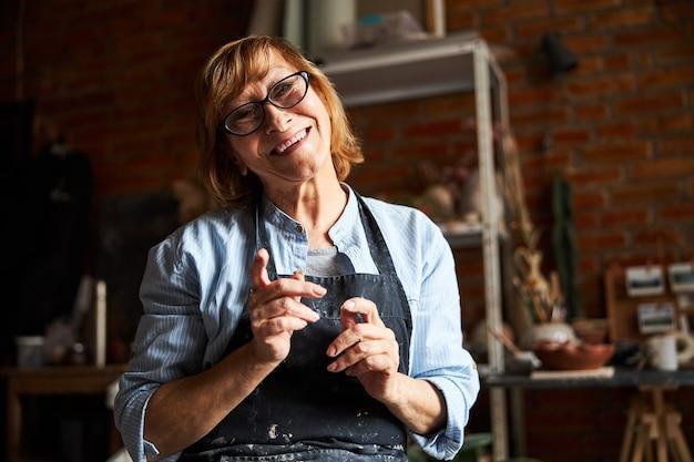 Gioiosa vecchia donna artista di ceramica che guarda l'obbiettivo e sorridente mentre si lavora in studio di ceramica