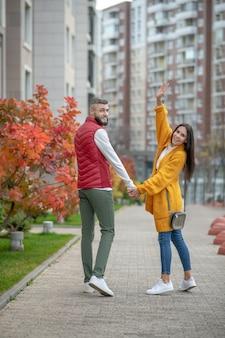 Uomo e donna gioiosi e piacevoli che si rivolgono a te mentre fai una passeggiata lungo la strada
