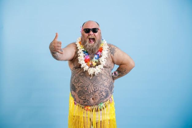 L'uomo grassoccio allegro con gli occhiali da sole in gonna d'erba mostra il gesto di saluto di shaka su fondo blu