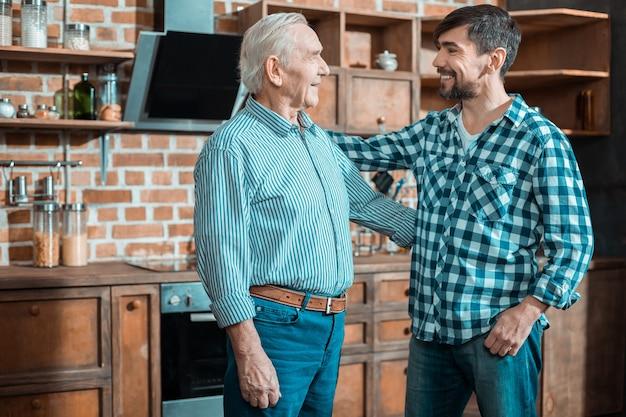 Gioioso uomo felice positivo guardando suo padre e sorridendo mentre lo abbraccia