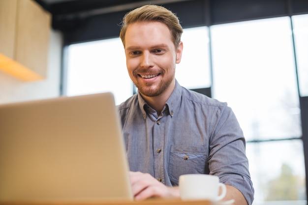 Uomo bello positivo gioioso utilizzando un computer portatile e lavorando sorseggiando un caffè nella caffetteria