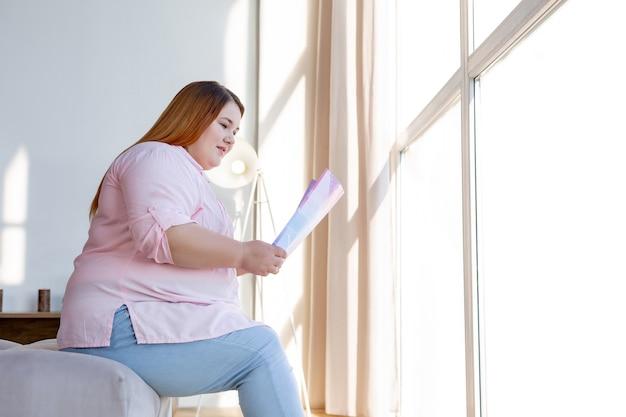 Gioiosa donna positiva che tiene in mano una rivista mentre è concentrata sulla lettura