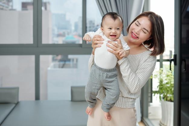 Gioiosa bella donna vietnamita che trasporta il suo bambino in maglietta di cotone e pantaloni di flanella