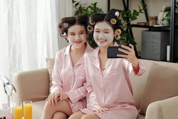 Gioiose e graziose giovani donne con bigodini e maschera di argilla sui volti che si fanno selfie su smartphone