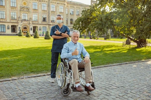 Uomo anziano allegro che recupera un paziente su una sedia a rotelle che sorride alla telecamera che mostra i pollici in su insieme