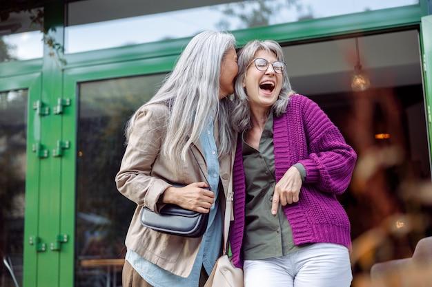 Le amiche anziane allegre con i capelli grigi naturali si divertono sulla strada della città