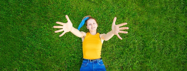 Ragazza allegra e sorridente si trova sull'erba guarda la telecamera fuori nel parco
