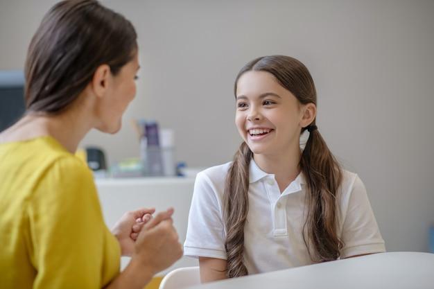 Ragazza sorridente allegra in maglietta bianca e psicologo della donna in camicetta gialla che si siede vicino a comunicare