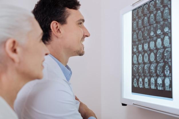 Medico maschio sorridente gioioso in piedi davanti alle immagini del cervello a raggi x e sorridente pur essendo felice per il suo paziente