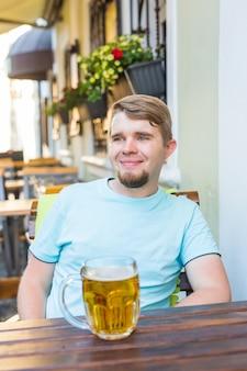 Uomo sorridente allegro che tiene un grande boccale di birra all'aperto